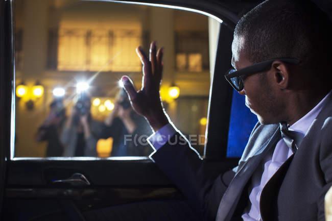 Знаменитості в лімузині розмахуючи на папарацці фотографів — стокове фото