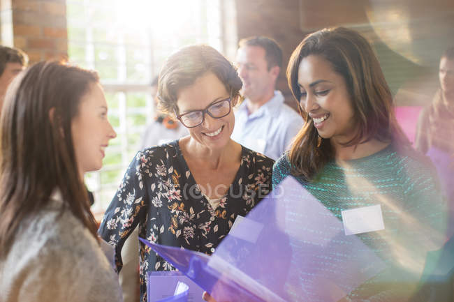 Smiling women looking at paperwork in community center — Stock Photo