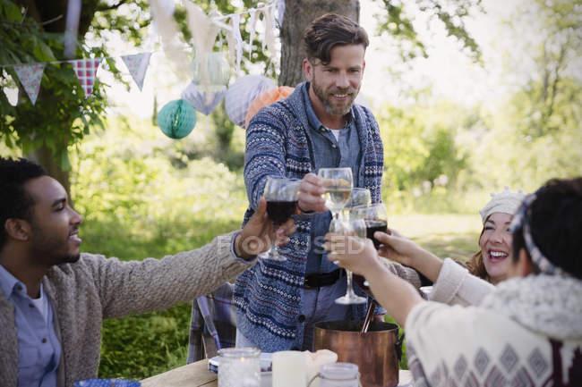 Amigos brindando com taças de vinho na mesa de festa de jardim — Fotografia de Stock
