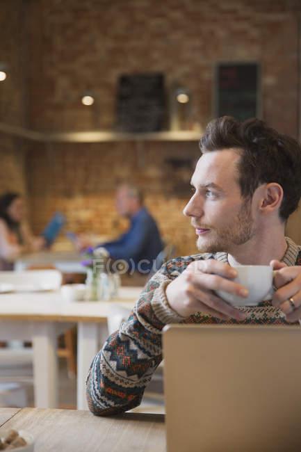 Hombre pensativo mirando hacia otro lado beber café en el ordenador portátil en la cafetería - foto de stock