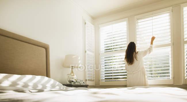 Frau im Bademantel Schlafzimmer-Fenster-Vorhänge öffnen — Stockfoto