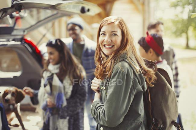 Portrait randonneur souriant tenant sac à dos avec des amis à l'arrière de la voiture — Photo de stock
