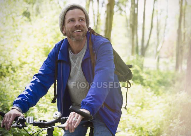 Smiling man mountain biking in woods — Stock Photo