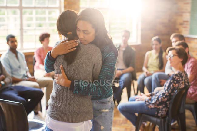 Жінки обіймає в групової терапії сесії — стокове фото
