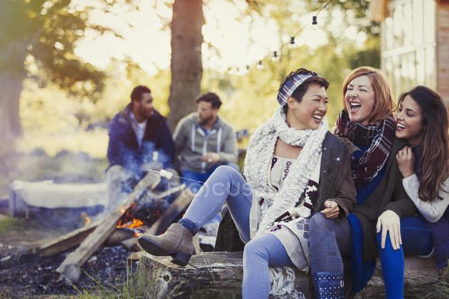 Amici femminili che ridono e tostatura marshmallow al falò — Foto stock