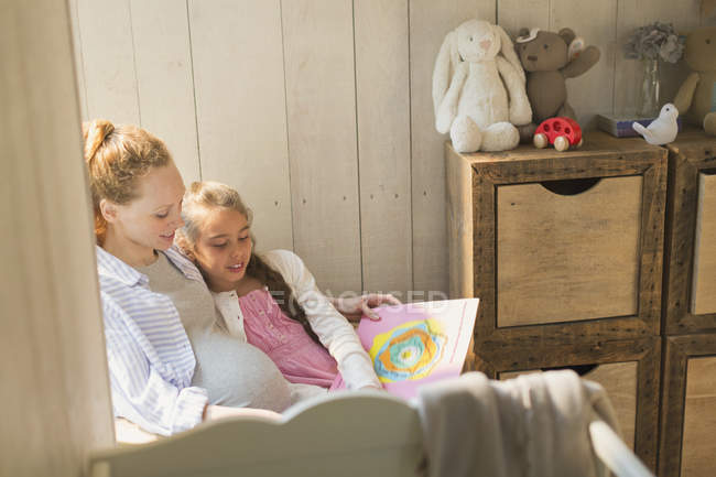 Pregnant mother and daughter reading story book in nursery — Stock Photo