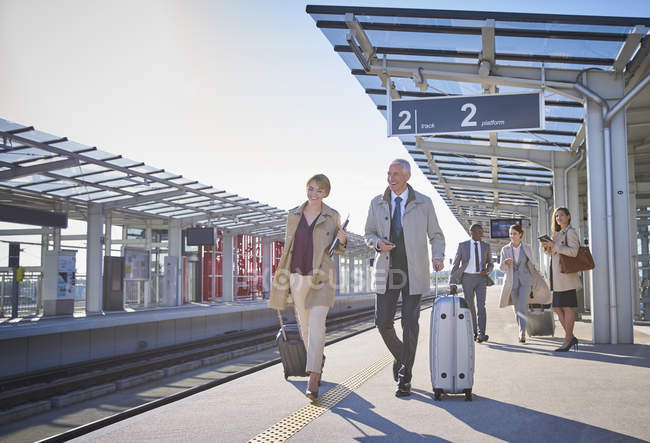 Business people walking pulling suitcases on sunny train station platform — Stock Photo