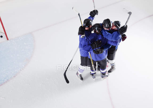 Hockey team in blue uniforms cheering celebrating on ice — Stock Photo