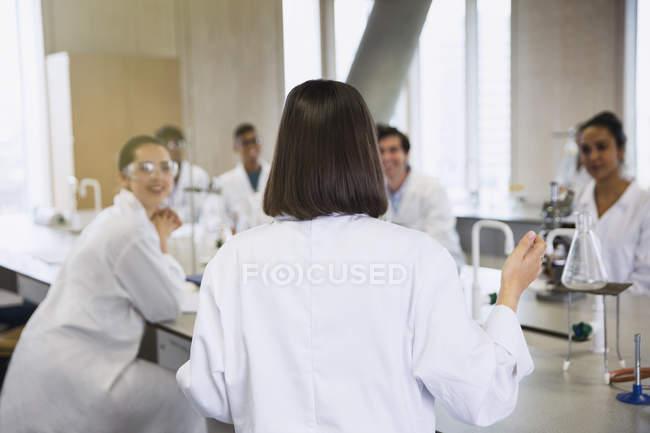 Жіночий студент провідних дослідницької групи у класі науки лабораторія — стокове фото