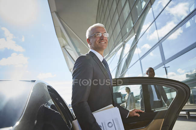 Smiling businessman arriving at airport getting out of town car — Stock Photo
