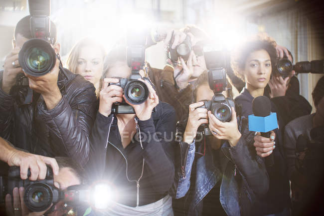 Portrait of serious paparazzi photographers pointing cameras — Stock Photo