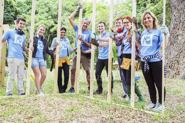 Портрет улыбающихся волонтеров, держащих раму на стройке — стоковое фото