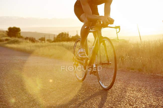 Männliche Radfahrer fahren Fahrrad auf sonnigen Sonnenaufgang Landstraße — Stockfoto