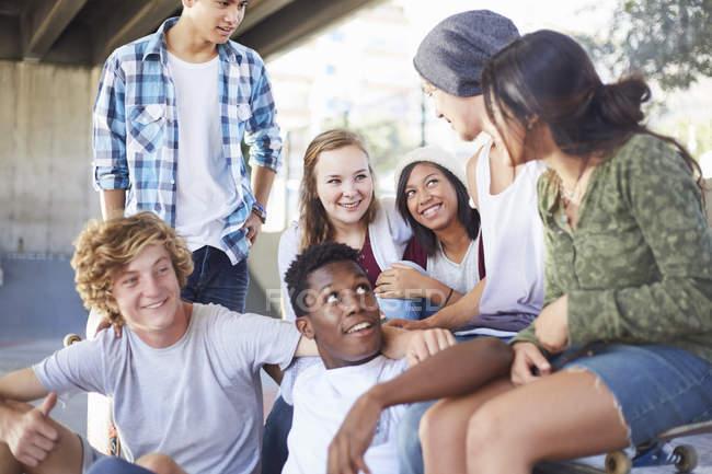 Друзья-подростки болтают в скейт-парке — стоковое фото