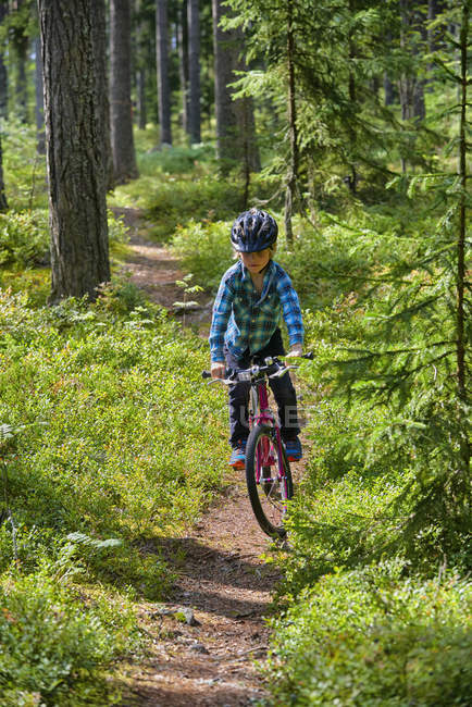 Boy riding bicycle on trail in woods — Stock Photo