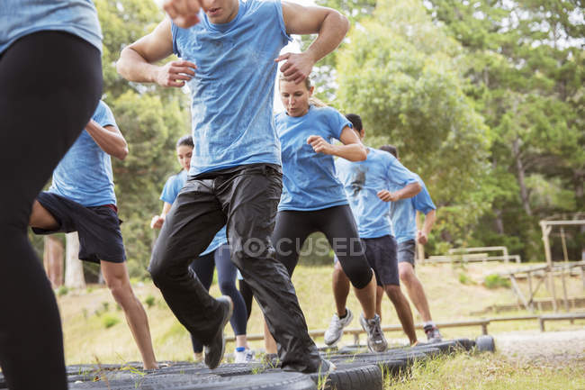 Determined people jumping tires on boot camp obstacle course — Stock Photo