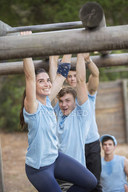 Smiling woman crossing monkey bars on boot camp obstacle course — Stock Photo