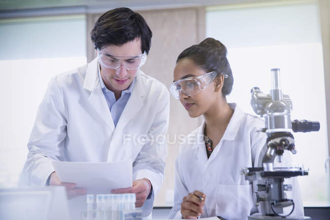 College students conducting scientific experiment at microscope in science laboratory classroom — Stock Photo