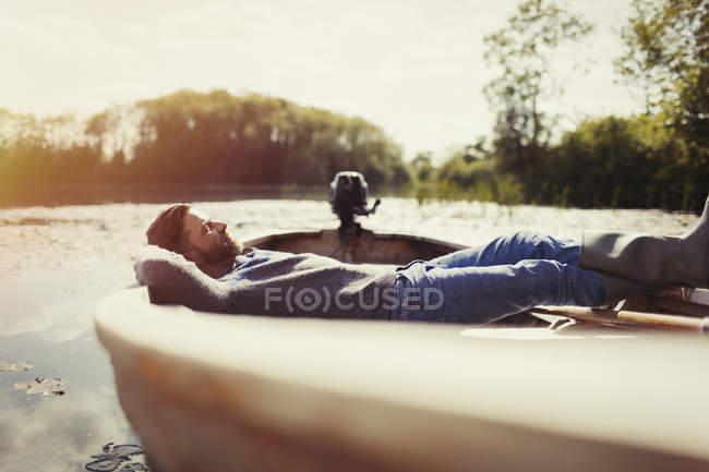 Homem sereno deitado relaxando em canoa no lago ensolarado — Fotografia de Stock