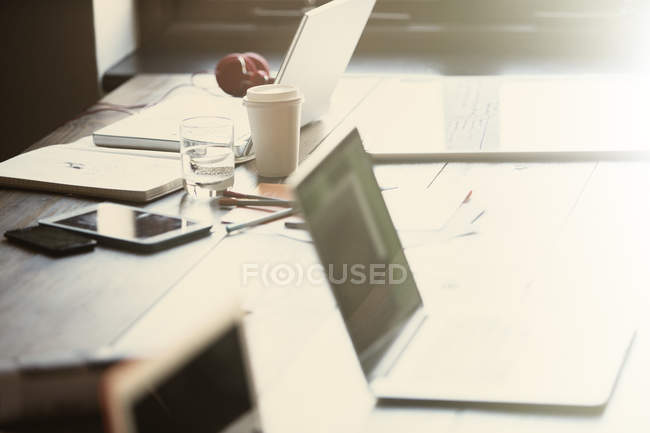 Laptops, tablet digital e papelada na mesa no escritório ensolarado — Fotografia de Stock