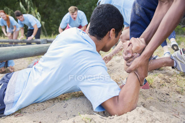 Teammate helping man on boot camp course — Stock Photo