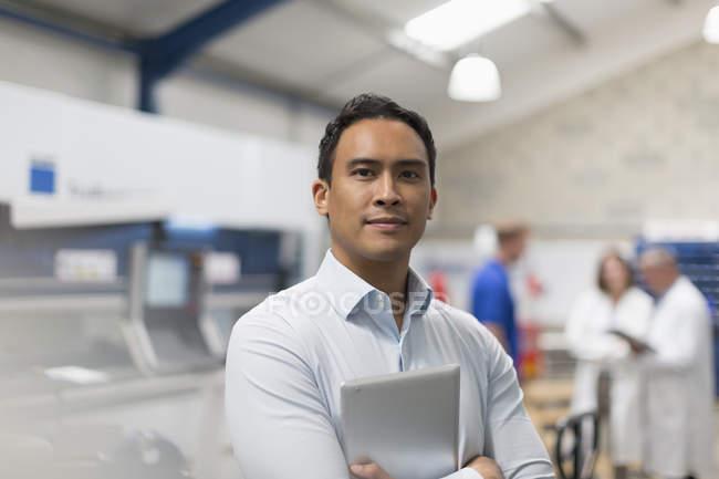 Gestionnaire de portrait confiant avec tablette numérique dans une usine d'acier — Photo de stock