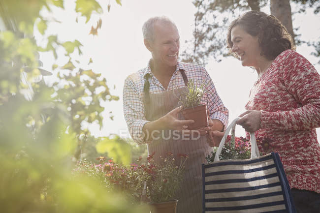 Nursery plant worker showing potted flowers to woman — Stock Photo