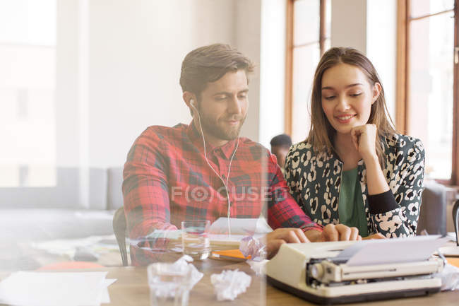 Creative business people working at typewriter at modern office — Stock Photo
