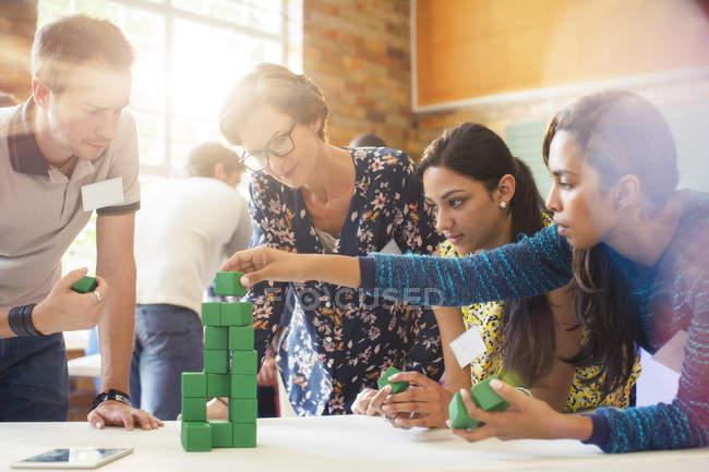 Gens d'affaires créatives empiler les blocs verts — Photo de stock