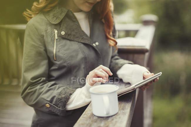 Femme buvant du café à l'aide d'une tablette numérique au balcon balustrade — Photo de stock