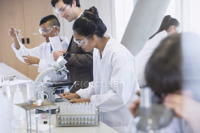 Étudiantes menant des expériences scientifiques en classe de laboratoire de sciences — Photo de stock