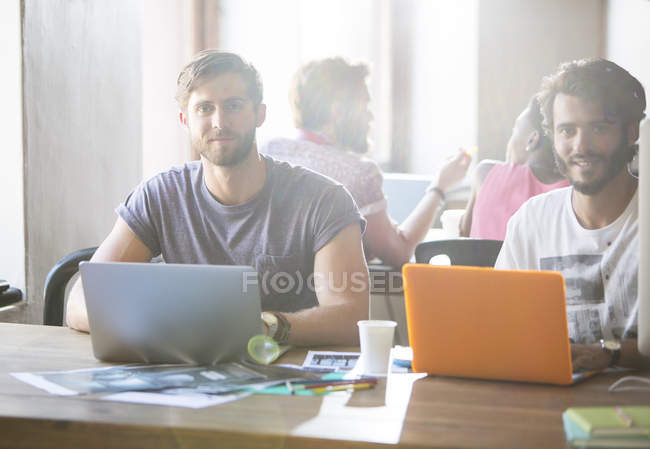 Portrait confident creative businessmen working at laptops in office — Stock Photo