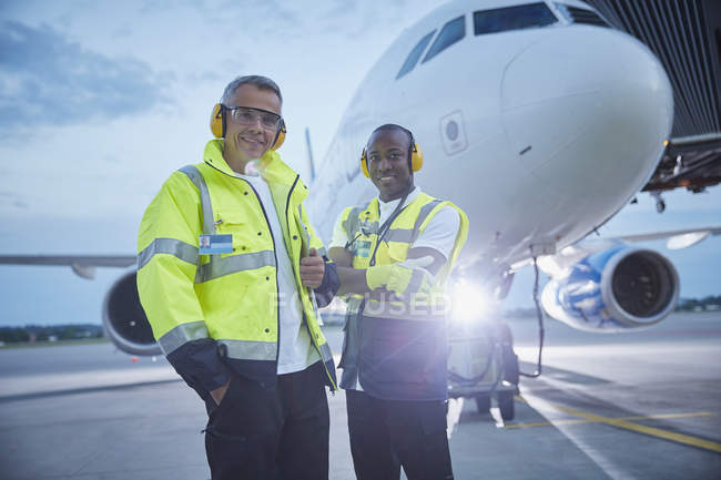 Portrait confident air traffic control ground crew workers near airplane on airport tarmac — Foto stock