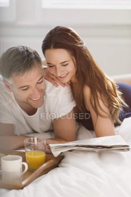 Paar liest gemeinsam Zeitung im Bett — Stockfoto