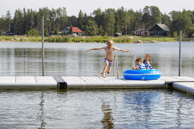 Boy jumping from dock into lake — Stock Photo