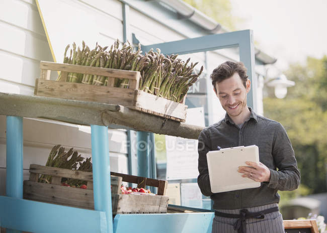 Працівник ринку фермер з буфера обміну перевірка інвентаризації поруч зі спаржею — стокове фото