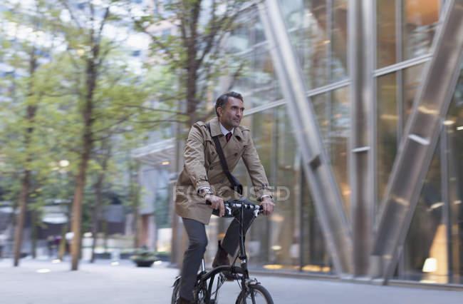 Корпоративный бизнесмен катается на велосипеде за пределами современного здания — стоковое фото