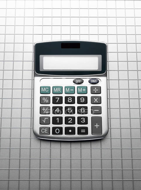 Calculator on grid gray background — Stock Photo