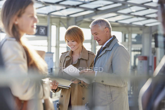 Business people reviewing paperwork in airport — Stock Photo