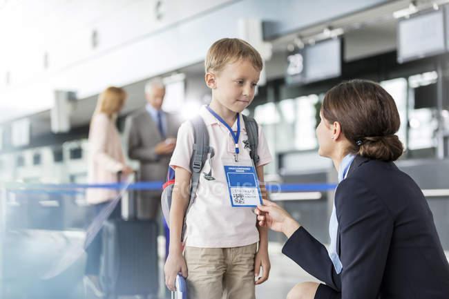 Auxiliar de vuelo, hablar con el viajero de niño en el aeropuerto - foto de stock