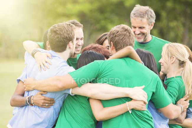 Team hugging in huddle during daytime — Stock Photo