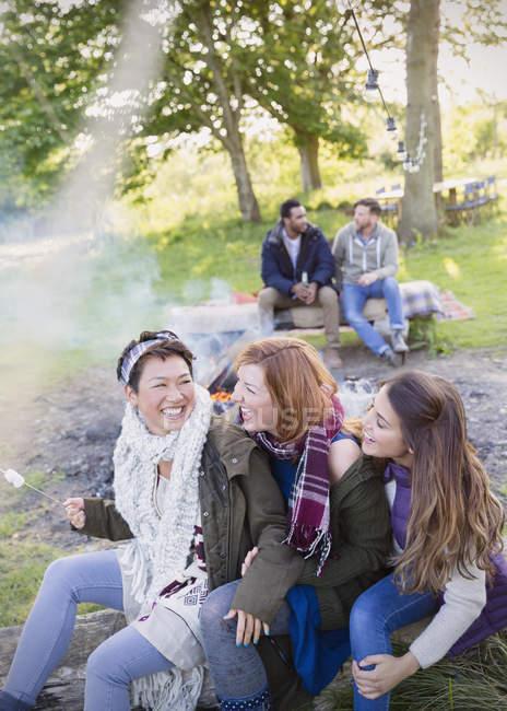 Amigos riendo tostando malvaviscos en la fogata - foto de stock