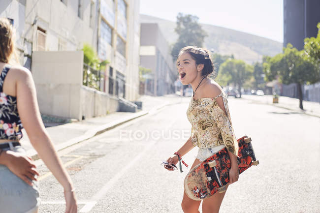 Teenage girl with skateboard on sunny urban street — Stock Photo