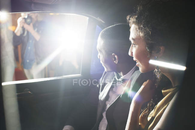 Celebrity couple in limousine arriving at red carpet event — Stock Photo