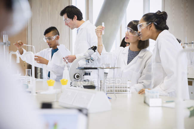 College students conducting scientific experiment in science laboratory classroom — Stock Photo