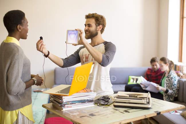 Creative businessman holding digital tablet and headphone — Stock Photo