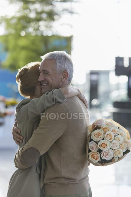 Paar mit Rosenstrauß umarmt — Stockfoto