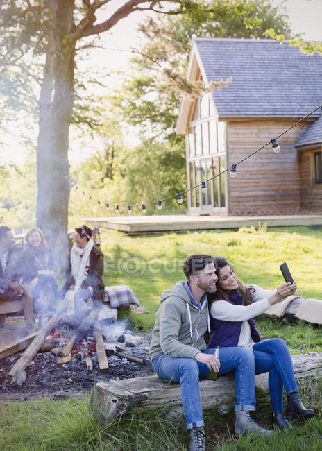 Couple taking selfie with camera phone at campfire outside cabin — Stock Photo