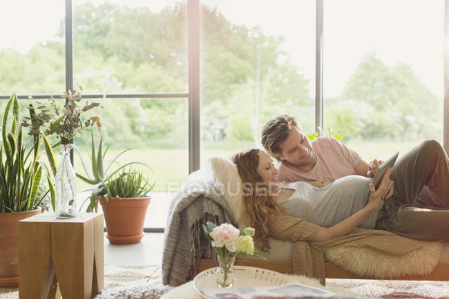 Pregnant couple laying using digital tablet in living room — Stock Photo