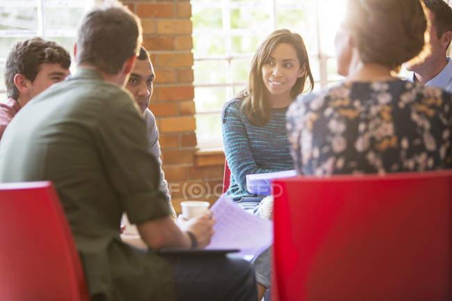 Женщина улыбается и слушает на сеансе групповой терапии — стоковое фото